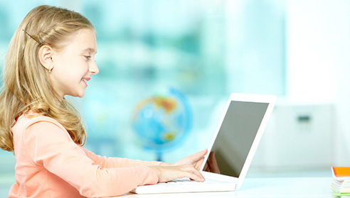 Portrait of smart schoolgirl sitting in classroom and typing